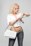 卷曲金发碧眼的女人,蓝色牛仔裤画象一件白革夹克夹克的,反映了太阳镜,拿着一个白革袋子 免版税库存图片