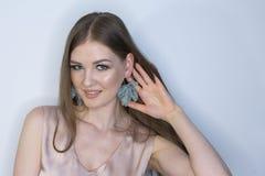卷曲长发白肤金发的年轻模型 有卷曲完善的发型有限的景深的秀丽女孩 图库摄影