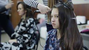 卷曲青少年的女孩头发的专业美发师美发师 影视素材
