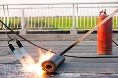 卷有丙烷小型发焰装置的屋顶设施 免版税库存照片