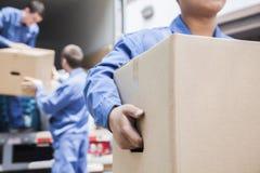 卸载一辆移动货车的搬家工人 免版税库存照片