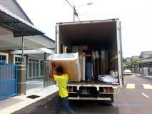 卸载一辆移动货车的搬家工人 库存图片