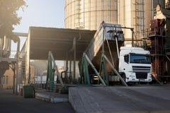 卸载五谷卡车在举起水力平台卸载机的电梯 在大海的粮食作物转船 免版税库存图片