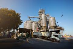 卸载五谷卡车在举起水力平台卸载机的电梯 在大海的粮食作物转船 免版税库存照片