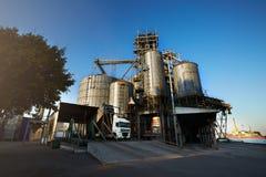 卸载五谷卡车在举起水力平台卸载机的电梯 在大海的粮食作物转船 库存照片