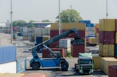 卸载从一辆卡车的机器容器货物在一个铁路集中处 免版税库存照片