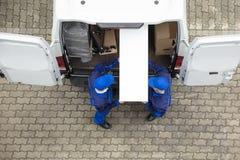 卸载从车的两个送货人家具 免版税库存照片