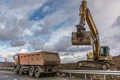 卸载土和石头在一辆卡车的挖掘机在工地工作 库存照片