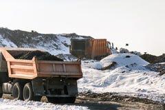 卸载在巨大的有益健康的积土的翻斗车废物 危机生态学环境照片污染 过时技术 免版税库存照片