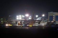 卸载在晚上的机场操作重的货物航空器 库存照片