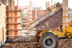 卸载石渣、沙子和石头的倾销者卡车在建造场所 Bricklayering和工作在建造场所 免版税库存照片