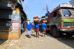 卸载粗麻布的顶头装载工作者从一辆卡车在市场上请求 库存照片