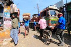 卸载粗麻布的顶头装载工作者从一辆卡车在市场上请求 免版税库存图片