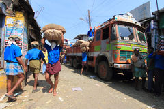卸载粗麻布的顶头装载工作者从一辆卡车在市场上请求 库存图片