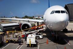 卸载行李的飞机在机场 免版税库存图片