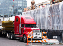 卸载金属的红色半卡车在cit的建筑边种田 免版税图库摄影
