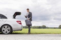 卸载从失败的汽车的全长年轻商人手提箱在乡下 图库摄影