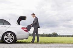 卸载从失败的汽车的年轻商人全长侧视图行李在乡下 免版税库存照片