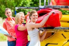 卸载从小船拖车的三名妇女皮船 免版税图库摄影