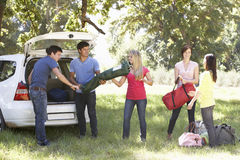 卸载从汽车后车箱的小组年轻朋友野营的设备  免版税库存照片