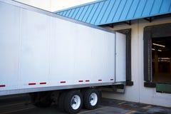 卸载货物的半拖车在有开放的门的码头仓里 库存照片
