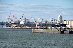 卸载货船的浮船和起重机在纽约哈勃 免版税库存图片