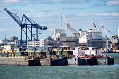 卸载货船的浮船和起重机在纽约怀有 免版税库存照片