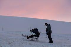 厄尔布鲁士山,俄罗斯,残疾人设法乘坐在一个雪橇的一个雪橇山 免版税库存照片