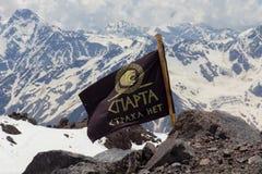 2014 07厄尔布鲁士山,俄罗斯:斯巴达旗子在风开发 库存图片