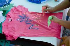 厄梅尔,内盖夫,以色列-两只手8月15, :成人和孩子同时画油漆管在桃红色T恤杉的, 2015年 免版税库存照片