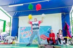 厄梅尔,以色列-人-玩杂耍在与一条白色长卷毛狗的阶段的小丑和两助理, 2015年7月25日 免版税库存照片