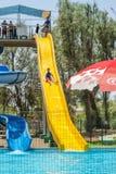 厄梅尔,以色列- 2015年7月25日在以色列孩子步行沿着向下在室外水池的黄色水滑道 免版税库存图片