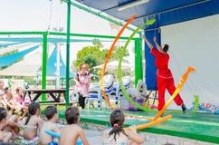 厄梅尔,以色列-跳跃与在露天舞台在孩子前面, 2015年7月25日的色的丝带的红色和服的女孩体操运动员 免版税库存照片