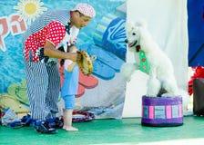 厄梅尔(啤酒舍瓦),有使用与一条白色长卷毛狗的孩子的以色列小丑, 2015年7月25日 免版税库存照片