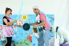 厄梅尔(啤酒舍瓦),以色列两在以色列扮小丑,使用与小孩和一条白色长卷毛狗, 2015年7月25日的男人和妇女 图库摄影