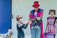 厄梅尔(啤酒舍瓦),以色列-两在以色列扮小丑,一个男人和一名妇女、一个男孩和一条白色长卷毛狗在白色背景2015年7月25日 免版税图库摄影