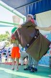 厄梅尔(啤酒舍瓦),以色列-小丑、男孩、长卷毛狗和一个大老手提箱在夏天阶段, 2015年7月25日 库存照片