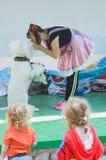 厄梅尔(啤酒舍瓦),以色列-小丑妇女、白色长卷毛狗和两个孩子-观察者后面2015年7月25日在以色列 库存图片