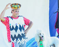 厄梅尔(啤酒舍瓦),以色列-扮小丑与网球和一条白色长卷毛狗在阶段, 2015年7月25日 库存图片