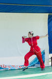 厄梅尔(啤酒舍瓦),以色列-有一把剑的女孩体操运动员在阶段与一个白色屏幕, 2015年7月25日的猩红色和服 库存图片