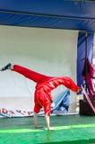 厄梅尔(啤酒舍瓦),以色列-猩红色和服的女孩体操运动员在与一个白色屏幕的阶段 他做着手倒立, 2015年7月25日 免版税库存图片