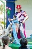 厄梅尔(啤酒舍瓦),以色列-男孩,小丑,在阶段展示魔术技巧的两白色长卷毛狗孩子的2015年7月25日 库存照片