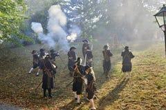 历史再制定天布尔诺 历史步兵服装攻击的演员与步枪 太阳通过火药smok发光 免版税库存图片