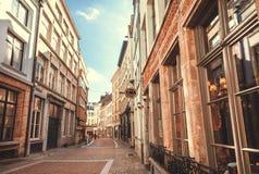 历史城市狭窄的街道有被修补的石头和餐馆的 免版税图库摄影