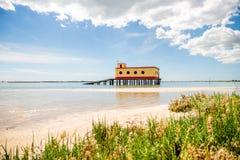 历史救生员大厦的晴朗的海滩视图在Fuseta, Ria福摩萨自然公园,葡萄牙 免版税图库摄影
