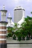 历史的伊斯兰教的清真寺Masjid Jamek塔在摩天大楼,马来西亚背景的吉隆坡  库存图片