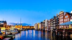 历史的房子行的夜景沿达姆拉克大街运河的,追溯到18世纪,在阿姆斯特丹的中心 免版税库存照片