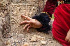 历史的礼服的夫人在石头雕刻的纹章学标志旁边 免版税图库摄影