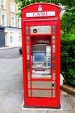 历史的红色电话箱子当现钞机,伦敦,英国 库存照片