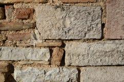 历史的自然石墙在阳光下 免版税库存图片